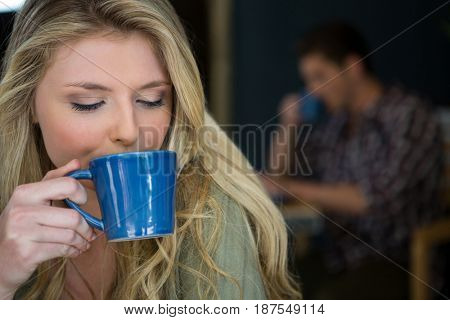 Close-up of young woman drinking coffee in cafeteria