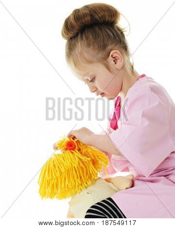 An adorable preschooler in an over-sized hairdresser's smock, curling her doll's yarn hair.  On a white background.