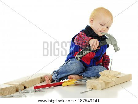 An adorable toddler hammering a large nail with his toy hammer.  On a white background.
