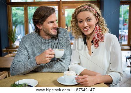 Portrait of happy young woman with man at table in coffee shop
