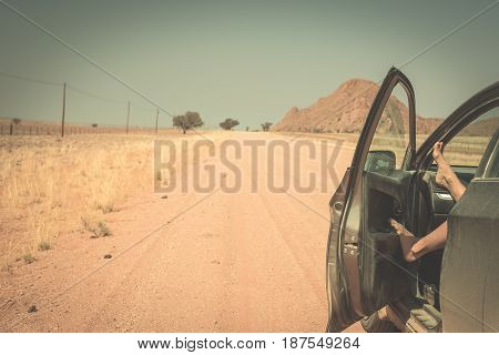 Woman's legs leaning out from car standing on gravel road in the Namib desert Namib Naukluft National Park main travel destination in Namibia Africa. Toned image people traveling and adventures.
