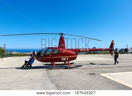 Benidorm Spain - May 13 2017: People and helicopter on a landing field. Benidorm helicopter tour is a tourist attraction on the Costa Blanca. Province of Alicante. Spain