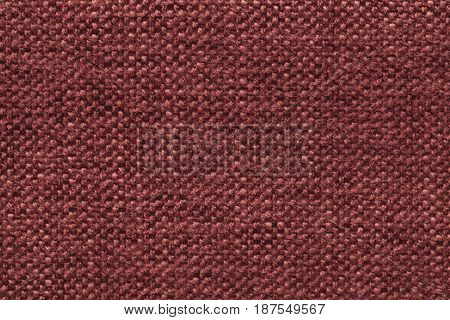 Dark red knitted woolen background with a pattern of soft fleecy cloth. Texture of maroon textile closeup.
