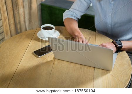High angle view of young man using laptop at table in coffee shop