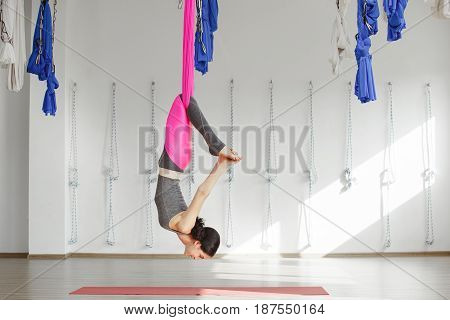 Girl in upside down pose on pink silk hammock, woman does aerial yoga exercises, meditates in calm position with bent legs. Reclining angle position in aerial antigravity yoga.