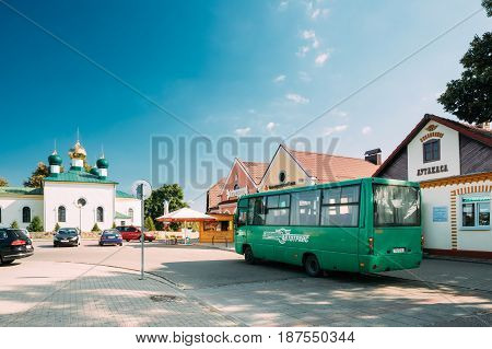 Mir, Belarus - September 2, 2016: Public Bus Car Parked Near Bus Station And Old Orthodox Church Of The Holy Trinity In Mir, Belarus. Famous Landmark In Sunny Summer Day With Blue Sky