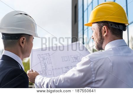 Back View Of Professional Architects In Hard Hats Discussing Project