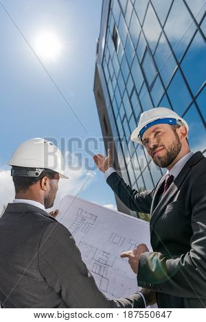 Low Angle View Of Professional Architects In Hardhats Working With Blueprint