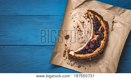 Top View Of Cheesecake On The Kraft Paper On The Blue Boards