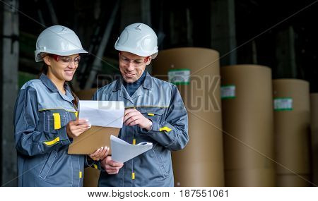 workers doing their job at a storage with paper rolls