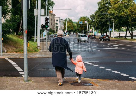 Vilnius, Lithuania  - July 5, 2016:  Elderly Woman With Little Child Girl Crossing Road At A Pedestrian Crossing In 16th Of February Street