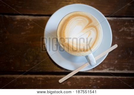 Top view of a beautiful white decorated cup with coffee cream. Food art creative concept