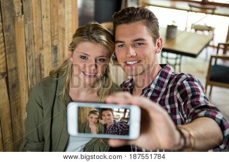 Smiling young couple taking selfie with mobile phone in cafeteria