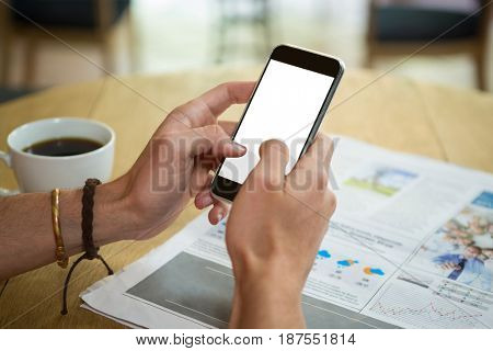 Cropped image of man using mobile phone at table in coffee shop