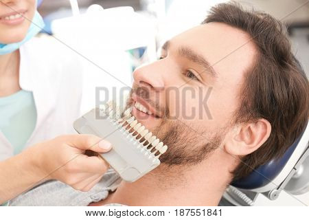 Dentist checking and selecting color of young man's teeth, closeup