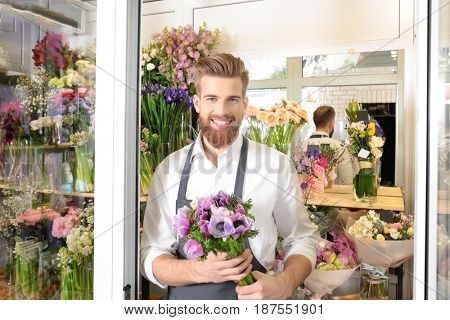 Young handsome florist with beautiful bouquet at flower shop