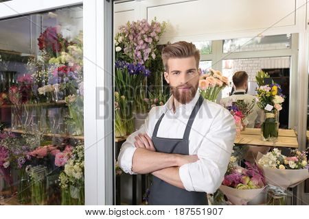 Portrait of young handsome florist with crossed arms in flower shop