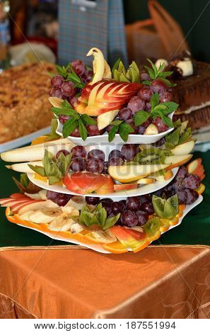 Fruit-cut fruits arranged on a three-tiered dish.