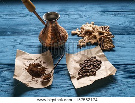 Coffee Beans, Ground Coffee, A Turk, A Silver Spoon For Kraft Paper And Christmas Cookies On The Blu