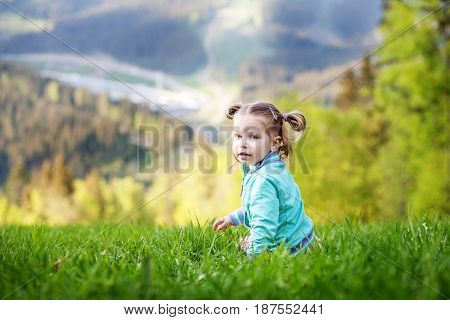 Small baby sitting on the grass. Summer. The concept of travel lifestyle and childhood.