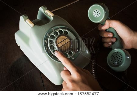 Close Up Of Hand Holding Old Black Rotary Telephone And Dialing A Number With Dust On Telephone On W