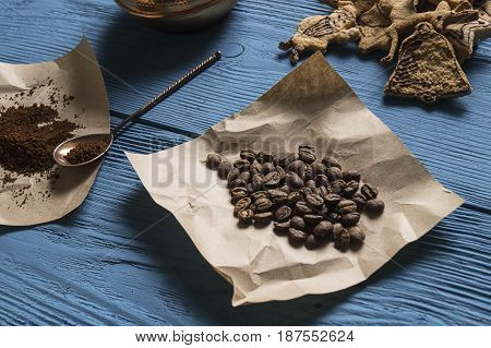 Coffee Beans, Ground Coffee, Silver Spoon On Kraft Paper And Christmas Cookies On The Blue Boards