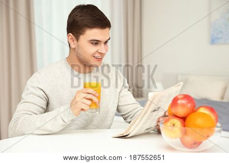 Young man drinking juice at home