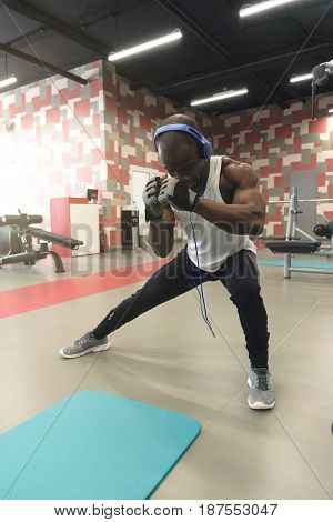 Great stretching. Side view of young handsome black man in sportswear and headphones doing stretching at gym