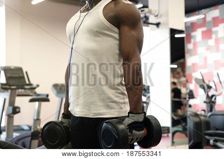 hard workout. Muscular black man in a white t-shirt doing exercises with dumbbells at gym