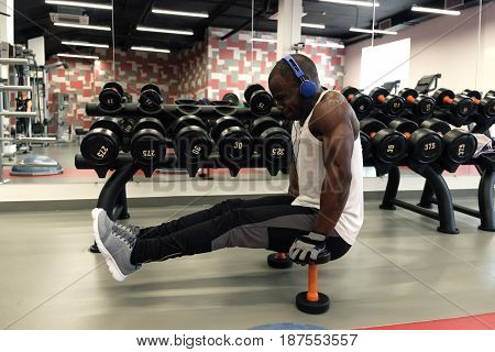 Muscular black man in a white t-shirt and blue headphones doing exercises with dumbbells in front of the mirror at gym