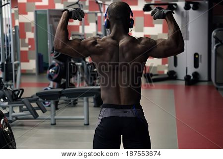 Athlete muscular bodybuilder posing in the gym. view from the back