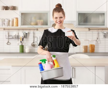 Young chambermaid with business card and cleaning supplies in kitchen