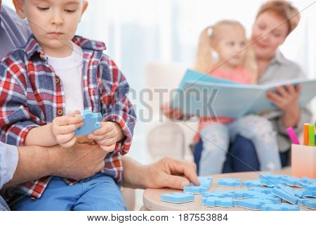 Cute little boy and grandfather playing with puzzle while his sister and grandmother are reading book