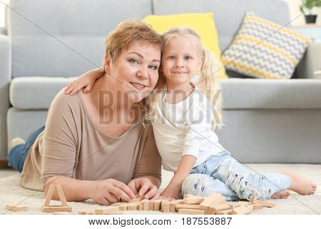 Happy senior woman and her granddaughter playing with wooden blocks at home