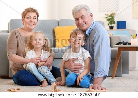 Happy senior couple and their grandchildren sitting on floor at home