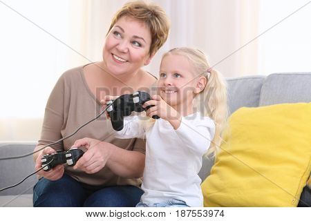 Senior woman and her granddaughter playing video game together at home