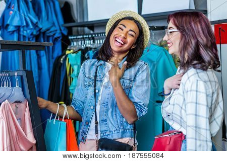 multicultural hipster girls choosing clothes in boutique fashion shopping girls concept