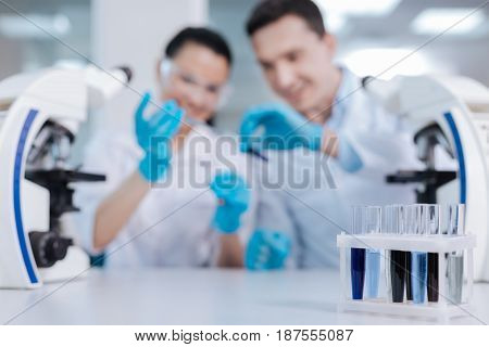 Working on result. Two competent scientists sitting on the background using assay reagents while doing experiment