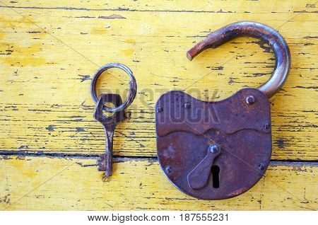 Old lock with a key on the background of wooden boards painted with yellow paint 2