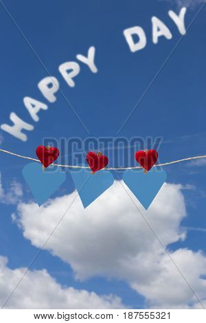 Three hearts with clothes pegs and three hearts of paper on a cord and the word happy day