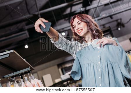 Young Hipster Girl Smiling And Taking Selfie In Boutique, Clothes Shopping Concept