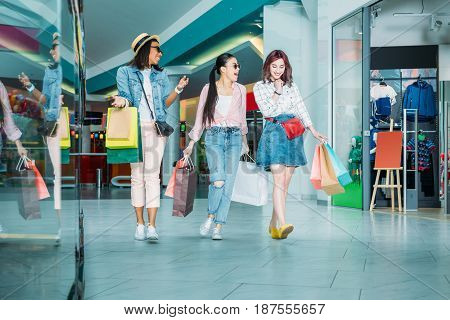 Happy stylish young women with shopping bags walking in shopping mall young girls shopping concept