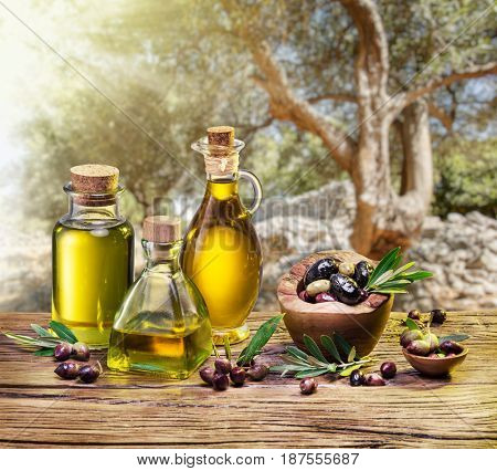 Olive berries in the wooden bowl and bottles of olive oil on the table. The beautiful sunset in the background.