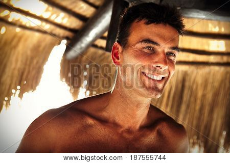 Beautiful smile, handsome and happy man outdoor shirtless. Holiday summer time. A positive and smiling man at the beach. Positive energy and vacation concept.
