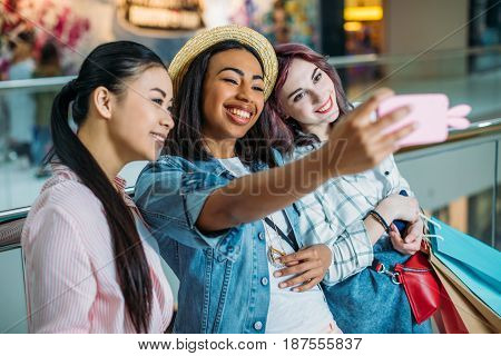 Smiling Young Women With Shopping Bags Taking Selfie, Young Girls Shopping Concept