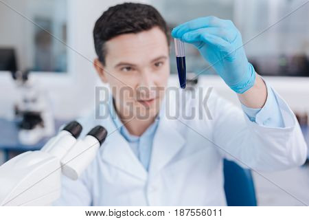 Wrinkling forehead. Serious practitioner looking attentively at his hand that keeping test-tube and working with chemical agent