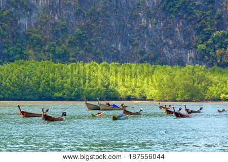 A wooden Thai boat against the background of the rock