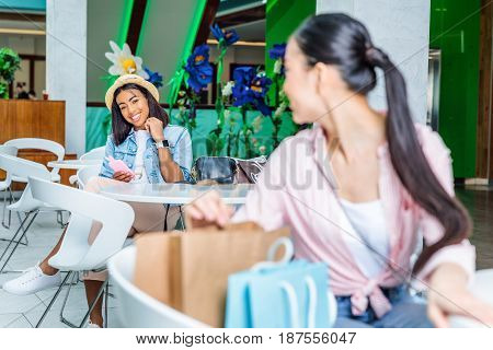 Smiling Young Women Looking At Each Other While Sitting In Shopping Mall