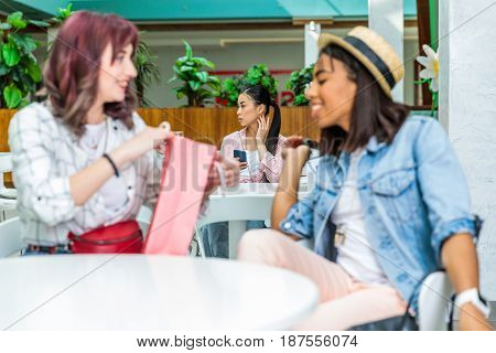 Smiling Young Women Sitting With Shopping Bag And Girl Using Smartphone Behind In Shopping Mall, You