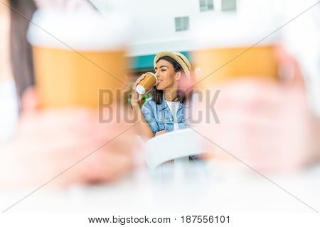 Smiling young african american woman in hat drinking coffee from paper cup